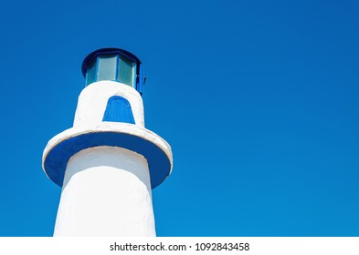 Beautiful white-blue lighthouse on a background of blue sky
