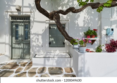 Beautiful whitewashed streets of Naoussa at Paros decorated with flowers