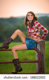 Beautiful and wholesome young woman wearing cowgirl boots and sitting on the coral fence.