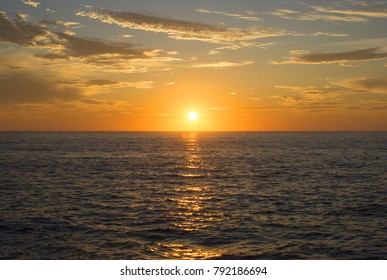 Beautiful wide angle setting golden sun centered over choppy ocean horizon