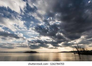 Beautiful wide angle view of a lake with an huge sky with clouds at sunset above skeletal trees