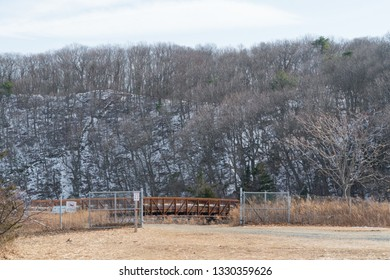 Beautiful wide landscape view of a snow covered hilltop in park past closing fence and foot bridge to cross river into woods.