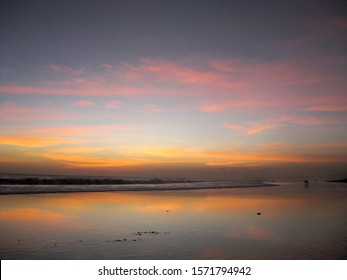 A beautiful wide shot of sea with sandy shore during sunset