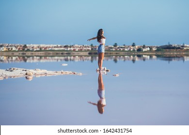 Beautiful wide vibrant summer view of las Salinas de Torrevieja, The Pink Lake Of Torrevieja, pink salt lagoon in Torrevieja, with female tourist reflection, Costa Blanca, province of Alicante, Spain