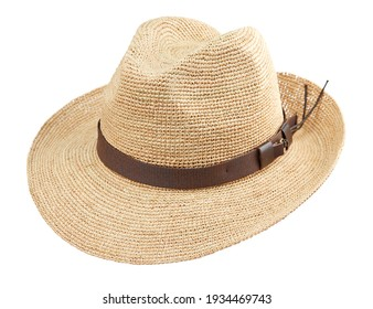 Beautiful wide-brimmed wicker hat fedora woven from straw, isolated on a white background. Beachwear and hats.
