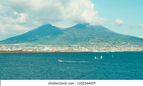 Beautiful widescreen view on volcano Vesuvius and Naples from Italy offshore. Wind surfers, fast boat on sea with Vesuvio crater and cloudy sky on background.
