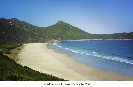 The beautiful wild beach of Sai Kung in Hong Kong, with white sand under a bright sunny sky.