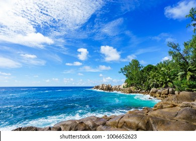 Beautiful and wild lonely beach with rough granite rocks, white sand, palm trees in a jungle and turquoise water of the indian ocean at police bay on the seychelles