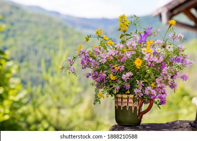 Beautiful Wild Spring Purple and Yellow Flowers  in a Small  Vintage Vase on a Summer Mountain Hills Background