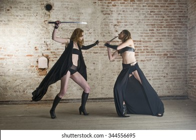 beautiful wild women fighting with swords front of the old red brick wall