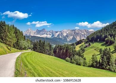 Beautiful winding mountain road in austrian alps with view on Dachstein massif, near Ramsau, Austria