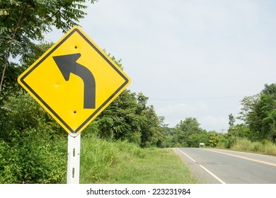 the beautiful winding road sign in yellow background and black arrow