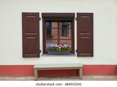 Beautiful window with flowers and shutters in the old town in Vilnius