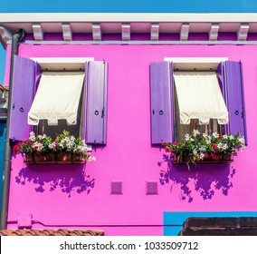 Beautiful windows with purple shutters and flowers vases in Burano, Italy