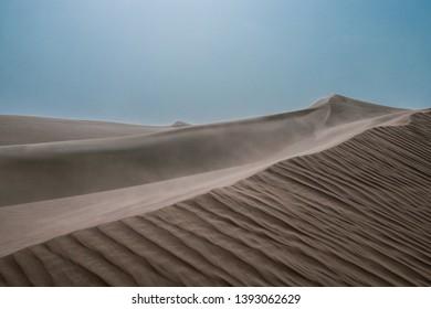 Beautiful and windy desert landscape. Light blue sky.