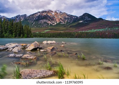 Beautiful windy and relaxing lake in the front with some rocks. Colorful canvas.
