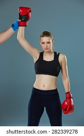 Beautiful winner. Beautiful blond hair woman in red boxing gloves standing on gray background. Concept of victory in the competition
