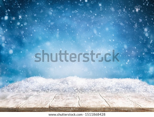 Beautiful winter background with wooden old desk and blurred blue sky. Winter, New Year and Christmas concept with snowy background.
