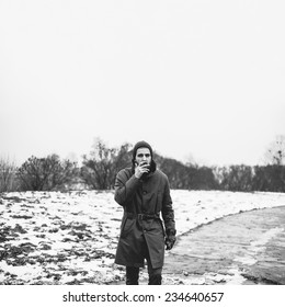 Beautiful winter brutal man with a cigarette