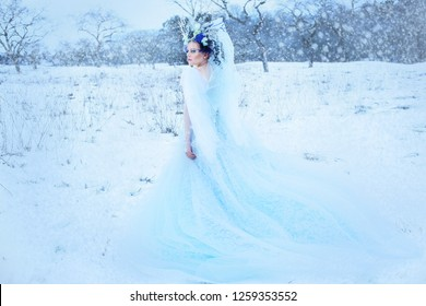 beautiful winter fairy in crown and light blue dress walking over snow field Snow Queen concept