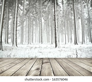 Beautiful winter forest with wood planks floor. Background is blurred