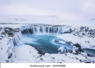 Beautiful winter Godafoss waterfall in Iceland, covered in snow