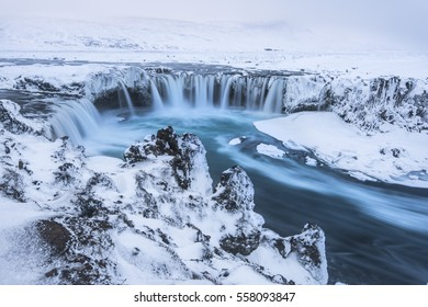 Beautiful winter Godafoss waterfall in Iceland, covered in snow, long exposure