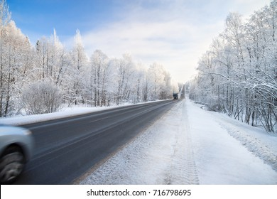 beautiful winter landscape with asphalt road,forest and blue sky.  frozen wintry day and path drive.