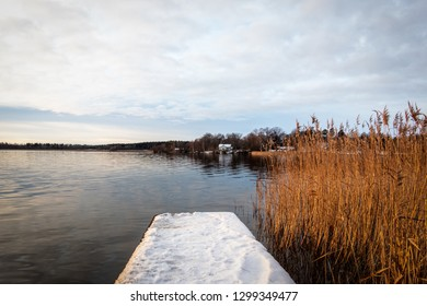 Beautiful winter landscape by the sea with snow on a jetty and rural horizon in the background.
