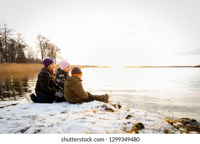 Beautiful winter landscape by the sea with a woman and children sitting in the snow on a rock looking at a bright sunset reflecting in the water.