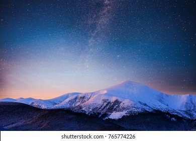 Beautiful winter landscape in the Carpathian mountains. Vibrant night sky with stars and nebula and galaxy.
