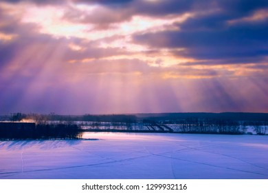 Beautiful winter landscape - covered with snow field and a few barren trees against the background of dramatic sky with sun rays strick through the dark clouds, Moscow region, Russia