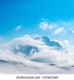 beautiful winter landscape of Dombaj with blue sky, clouds and descent from the mountain, Russia