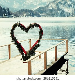 Beautiful winter landscape with pier and heart arch, Lake Bled, Slovenia. Square toned image, instagram effect