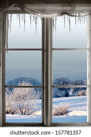 Beautiful winter landscape with rime frost in bushes and trees, seen through an old window with icicles
