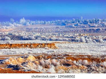 Beautiful winter landscape - small village and a field with frozen trees and grass against the background of blue foggy sky near Goreme, Cappadocia (Kapadokya), Central Anatolia, Turkey