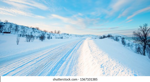 Beautiful winter landscape with snow and ice covered road - Arctic landscape    - Snow storm on the empty road - Snow covered road on a winter day - Tromso, Norway