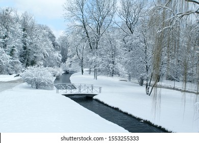 beautiful winter landscape with snowy trees in a park by a winding Isar river in Munich