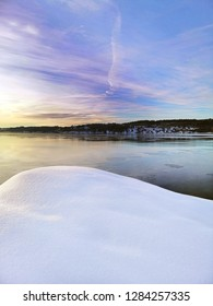 Beautiful winter landscape. A stone covered with snow in the foreground and the fjord and the city of Larvik in the background.