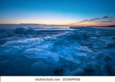Beautiful winter landscape with sunset sky and frozen lake. Composition of nature.