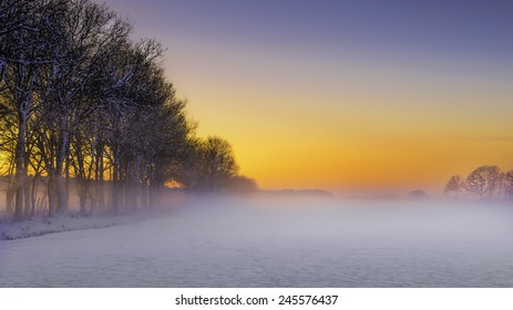 Beautiful winter landscape at sunset with snow and fog