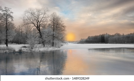 Beautiful winter landscape with trees covered in rime frost, and reflection in water of sunset over river partly covered with ice