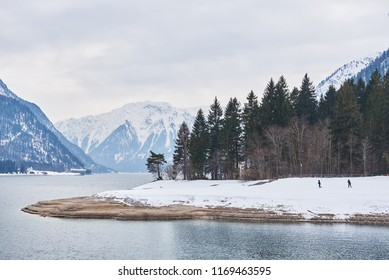 Beautiful winter landscape with two people at Achensee / Lake Achen, Austrian Alps. Neutral colors.