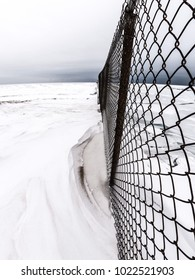 Beautiful winter landscape view along the shores of Lake Michigan with chain link fence jutting out along a snow covered beach and frozen snow covered blue ice and white cloudy sky above.