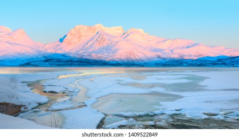 Beautiful winter lanscape with cracks on the surface of the turquoise (green) ice next to snowy mountains - Fjord and Frozen lake, Norway