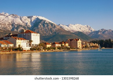 Beautiful winter Mediterranean landscape. Montenegro, Bay of Kotor. View embankment of Tivat city and snowy peaks of Lovcen mountains