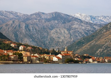 Beautiful winter Mediterranean landscape. Small town at the foot of the mountains.  Montenegro, Adriatic Sea, Bay of Kotor, Prcanj town