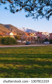Beautiful winter Mediterranean landscape with a village, snow-capped mountains and long shadows from trees on green grass. Montenegro, Tivat, the village of Donja Lastva