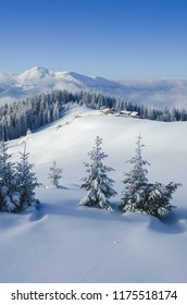 Beautiful winter mountain scenery. View of wooden huts and top. Sunny weather is a frosty day. Clear blue sky