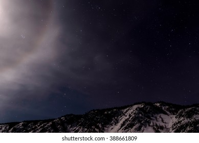Beautiful winter night landscape with mountains covered with snow and a part of the lunar halo against a background of stars and dark sky